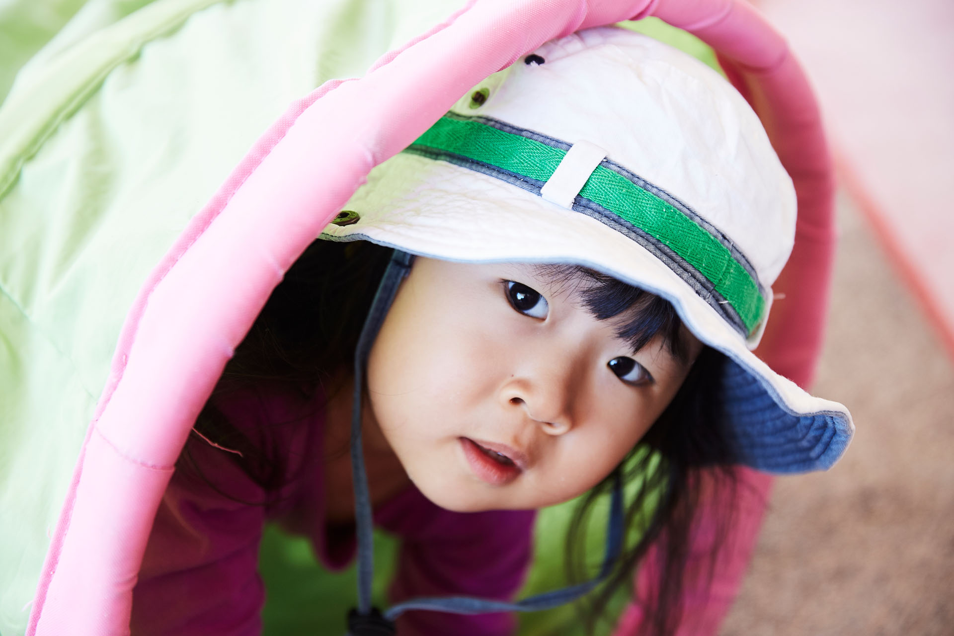 Child wearing hat peering from outside of play tunnel